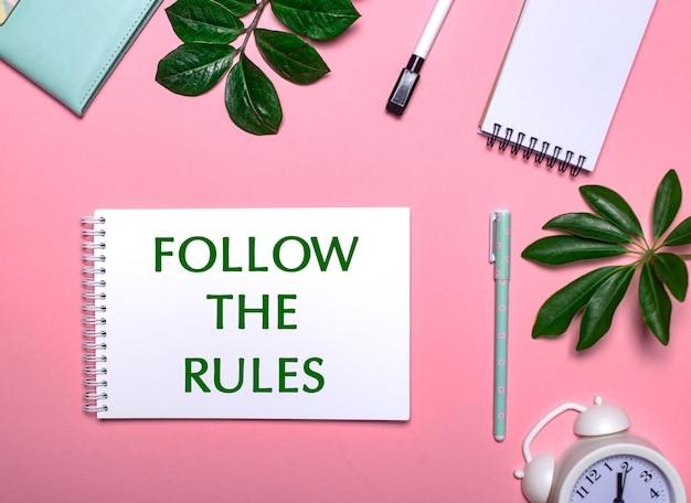 Follow the rules jest napisane kolorem zielonym na białym notesie na różowym tle, otoczonym notatnikami, długopisami, białym budzikiem i zielonymi listkami. koncepcja edukacyjna