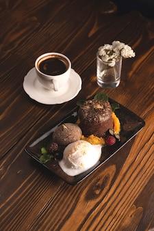 Fondant czekoladowy z lodami i jagodami na drewnianym stole w restauracji obok filiżanki kawy