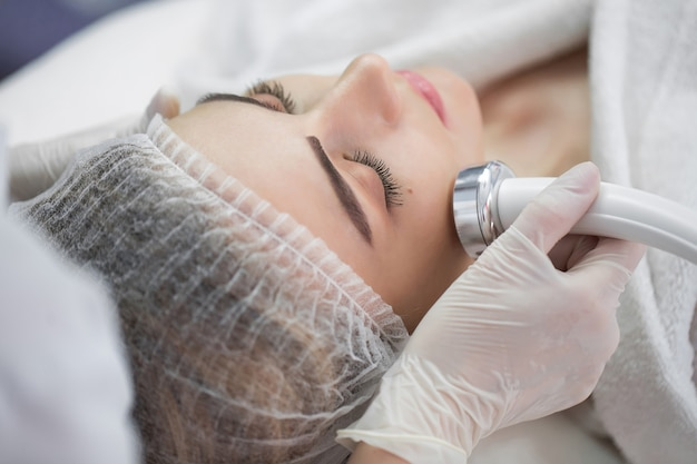 Fonoforeza hipersoniczna. model z zamkniętymi oczami, z profilu. klinika kosmetologiczna, zabieg. profil. służba zdrowia, przychodnia, kosmetologia