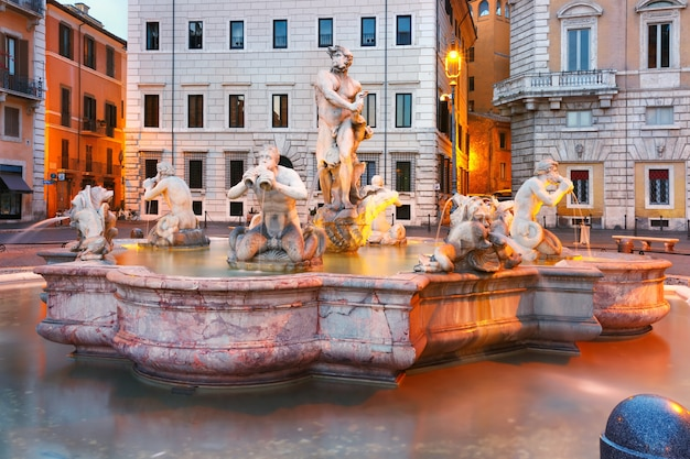 Fontana del moro z czterema trytonami wyrzeźbionymi na słynnym placu piazza navona podczas porannej niebieskiej godziny, rzym, włochy.
