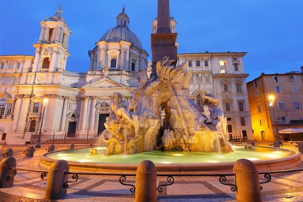 Fontanna czterech rzek i kościół sant agnese na słynnym placu piazza navona podczas porannej niebieskiej godziny, rzym, włochy.