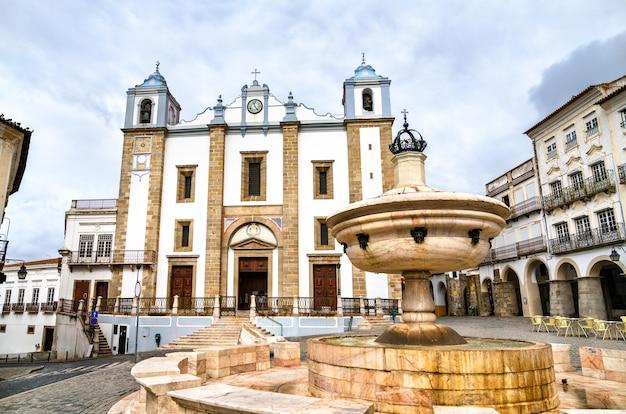 Fontanna i kościół santo antao na placu giraldo w evora. światowe dziedzictwo unesco w portugalii