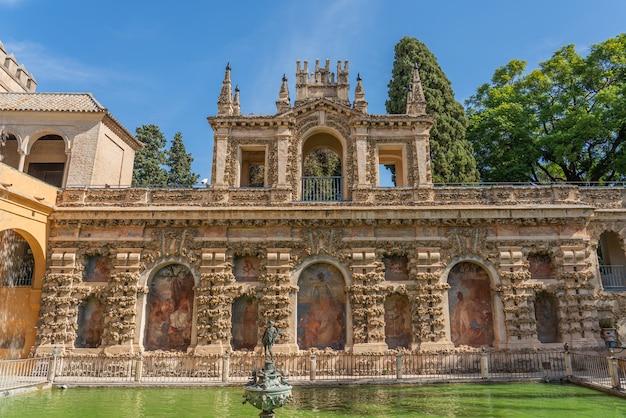 Fontanna z zabytkowym budynkiem z malowaniem na dziedzińcu pałaców real alcazar w sewilli, andaluzja, hiszpania
