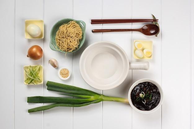 Food knolling asian noodle, flat lay concept składniki jajangmyeon lub jjajangmyeon, koreański makaron z sosem z czarnej fasoli. na białym drewnianym tle