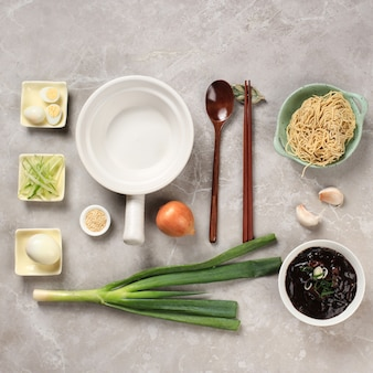 Food knolling asian noodle, flat lay concept składniki jajangmyeon lub jjajangmyeon, koreański makaron z sosem z czarnej fasoli. na szarym cementowym drewnianym tle