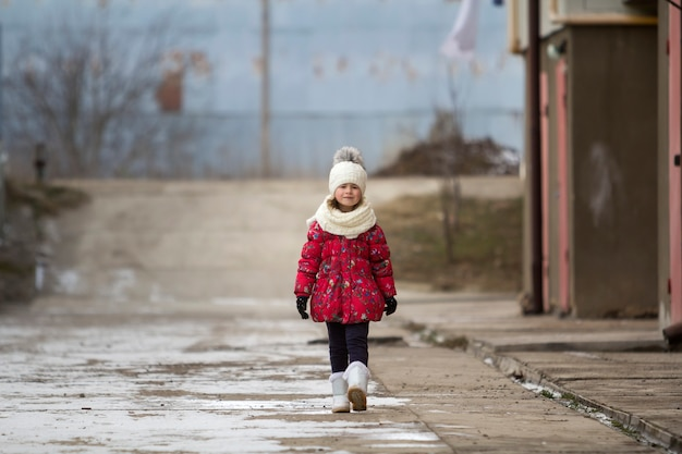 Fool-dług portret ładny mały młody śmieszne dziecko ładne dziewczyny w ładne ciepłe zimowe ubrania chodzenie pewnie samotnie na białym jasnym na zewnątrz niewyraźne kopia tło. zajęcia na świeżym powietrzu.