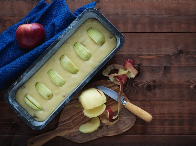 Foremkę z szarlotki na ciemnym drewnianym podkładzie przygotowaną do pieczenia z dekoracjami jabłkowymi. skopiuj miejsce.