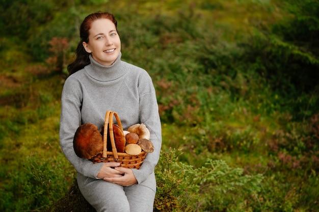 Forester kobieta siedzi w lesie z koszem grzybów koncepcja ekoturystyki