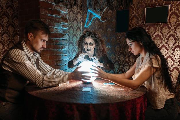 Foreteller przywołuje duchy nad kryształową kulą