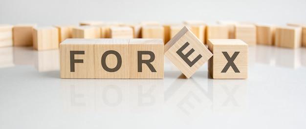 Forex - słowo drewnianych klocków z literami na szarym tle. odbicie napisu na lustrzanej powierzchni stołu. selektywne skupienie.