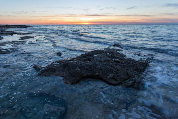 Formacje skalne na brzegu morza adriatyckiego w savudrija, istria, chorwacja podczas zachodu słońca