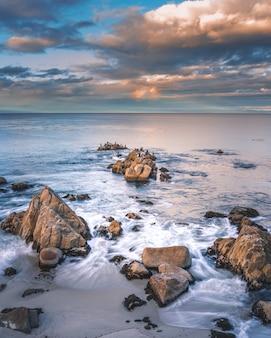 Formacje skalne w morzu pod białymi chmurami