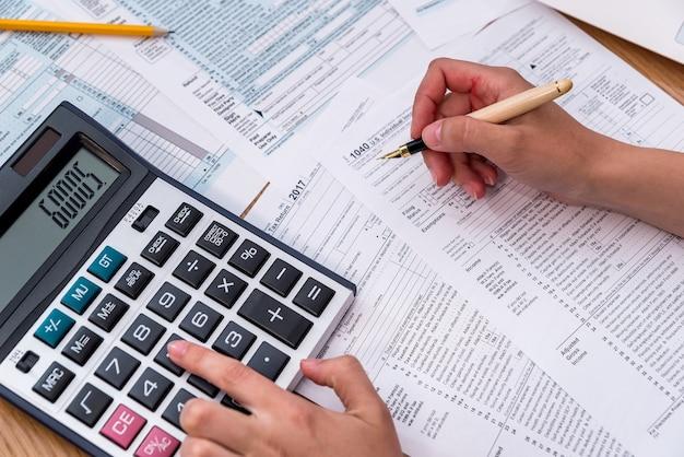 Formularz 1040 z kobiecą ręką, długopisem i kalkulatorem