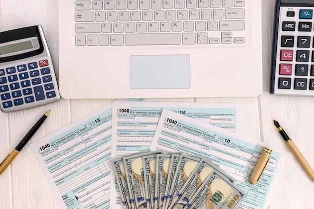 Formularz 1040 z laptopem i banknotami dolarowymi