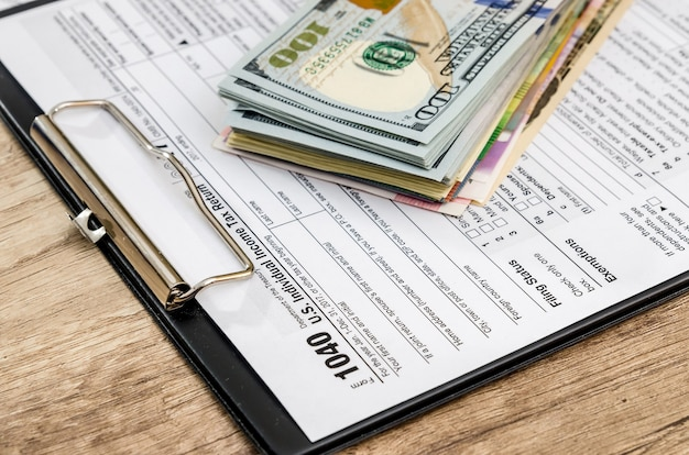 Formularz 1040 z różnymi banknotami na drewnianym stole