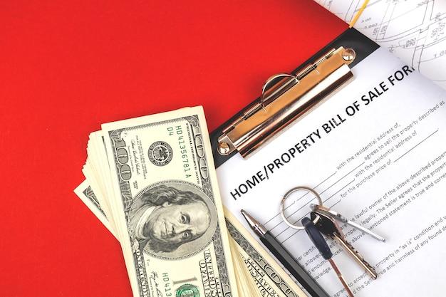 Formularz dowodu sprzedaży nieruchomości. klucze do domu, pieniądze i dokumenty projektowe dotyczące nieruchomości. zdjęcie z góry biurka