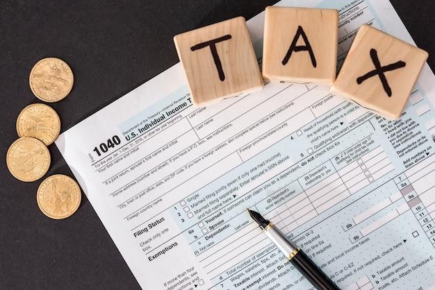 Formularz podatkowy 1040, drewniane kostki długopis i moneta na czarno