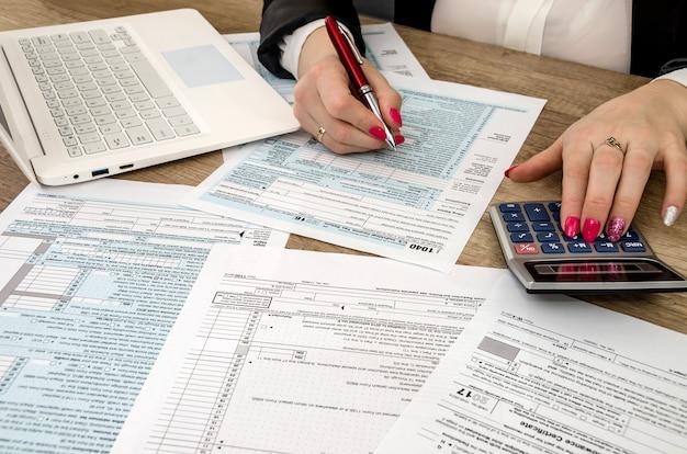Formularz podatkowy 1040 ludzkich rąk i laptopa