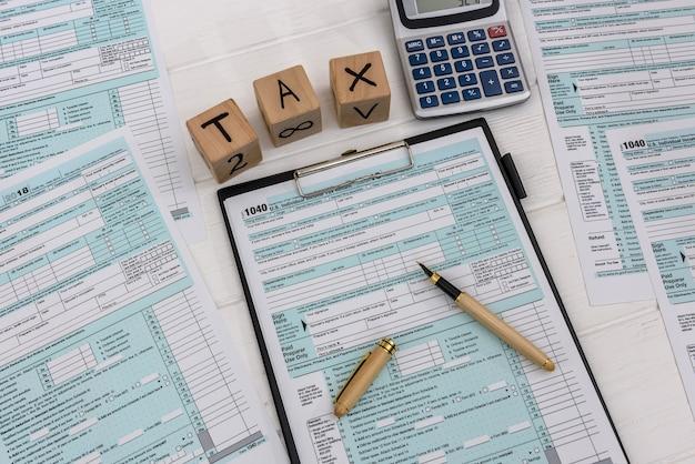 Formularz podatkowy 1040 na schowku z drewnianymi kostkami i kalkulatorem