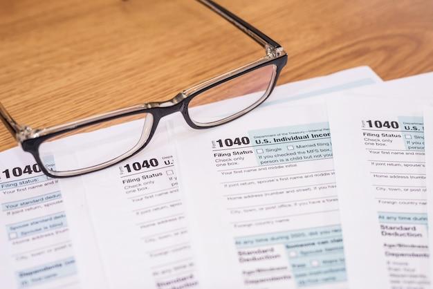 Formularz podatkowy 1040 w usa z okularami. koncepcja finansowa.