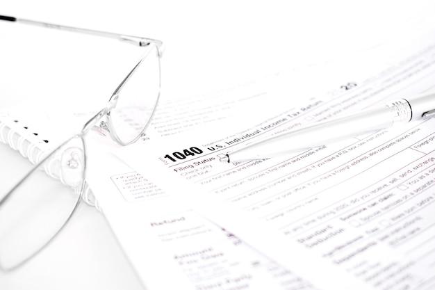 Formularz podatkowy 1040 w usa ze srebrnym długopisem i okularami