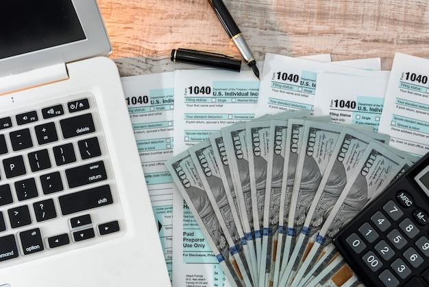 Formularz podatkowy 1040 z długopisem, dolarem i laptopem w biurze. czas podatkowy. koncepcja rachunkowości