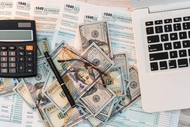 Formularz podatkowy 1040 z długopisem, dolarem i laptopem w biurze. czas podatkowy. koncepcja rachunkowości.