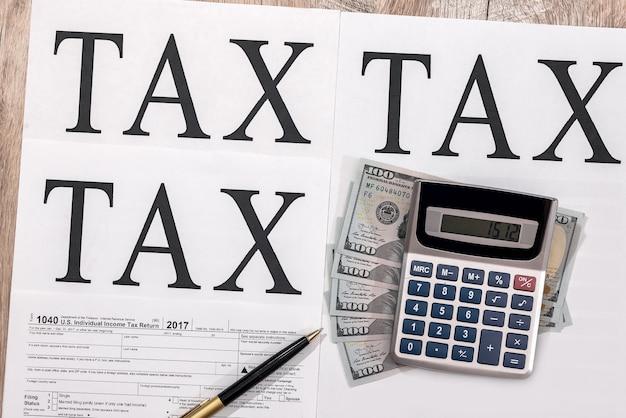 Formularz podatkowy 1040 z dolarami, kalkulatorem i długopisem