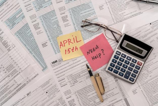"""Formularz podatkowy 1040 z kalkulatorem, długopisem i tekstem """"potrzebuję pomocy"""""""