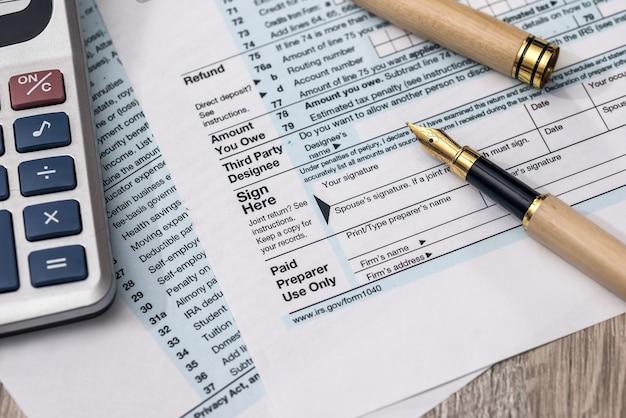 Formularz podatkowy 1040 z kalkulatorem i długopisem