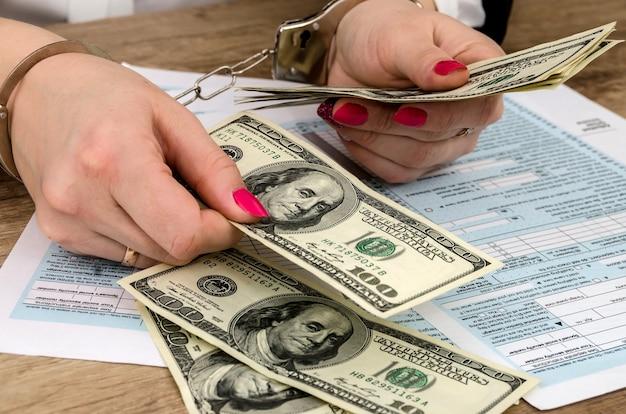 Formularz podatkowy, ręce w kajdankach, pieniądze