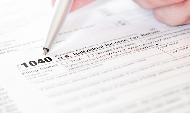 Formularz podatkowy us 1040 i przedsiębiorca trzymający pióro za znak