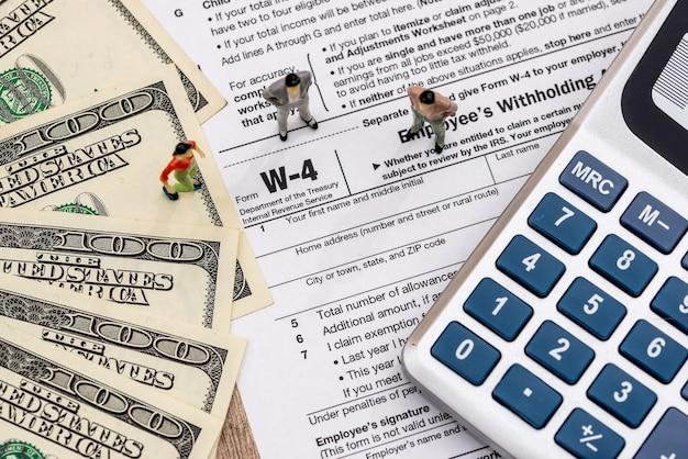 Formularz podatkowy w-4 zawierający minifigurki, dolary i kalkulator