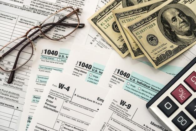 Formularz podatkowy z dolarem, kalkulatorem i długopisem