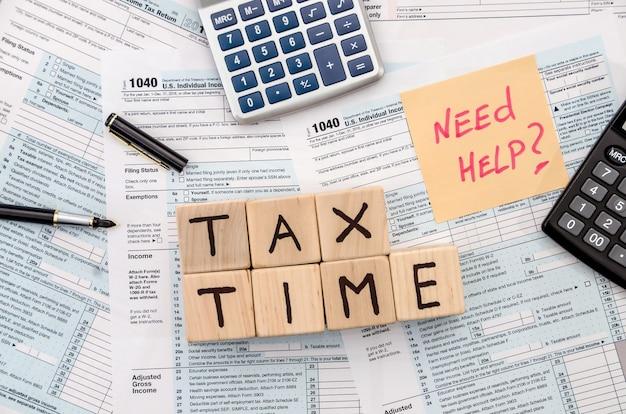 Formularz podatkowy z drewnianymi kostkami, naklejką, długopisem i kalkulatorem