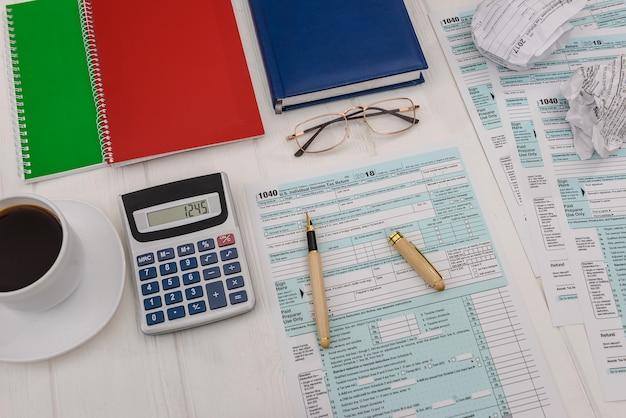 Formularz podatkowy z kalkulatorem i kawą na stole