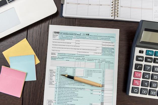 Formularz podatkowy zawierający kalkulator, laptop i długopis
