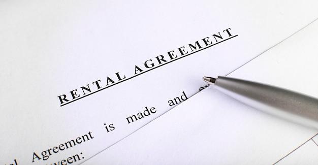 Formularz umowy najmu na pulpicie za pomocą pióra w biurze firmy przedstawiający koncepcję nieruchomości