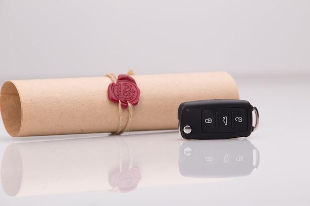 Formularz wniosku o kredyt samochodowy, długopis i klucz na drewnianym stole, widok z bliska