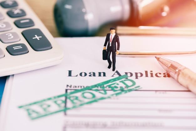 Formularz wniosku o pożyczkę z gumowym stemplem, na którym jest napisane: zatwierdzony kredyt, zatwierdzenie pożyczki finansowej