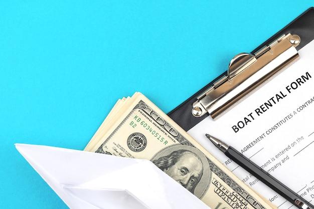 Formularz wniosku o wypożyczenie łodzi. schowek z oficjalną umową, długopisem i pieniędzmi. zdjęcie w widoku z góry