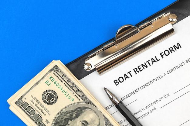 Formularz wypożyczenia łodzi. schowek z oficjalną umową, długopisem i pieniędzmi. zdjęcie w widoku z góry
