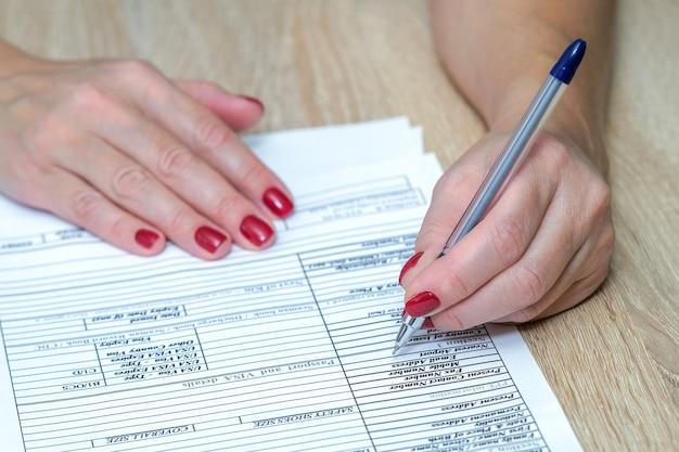 Formularz zgłoszeniowy dłoń trzymająca długopis gotowy do wypełnienia listy pytań formularz zgłoszeniowy