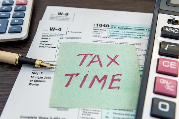Formularze finansowe podatku z piórem i kalkulatorem oraz naklejka z tekstem czas podatkowy. termin, formalności