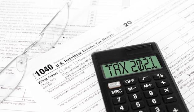Formularze podatkowe 1040, kalkulator z napisem tax 2021 i długopis na stole