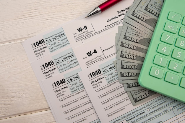 Formularze podatkowe 1040 z dolarami i kalkulatorem do wypełnienia w kwietniu. koncepcja podatków.