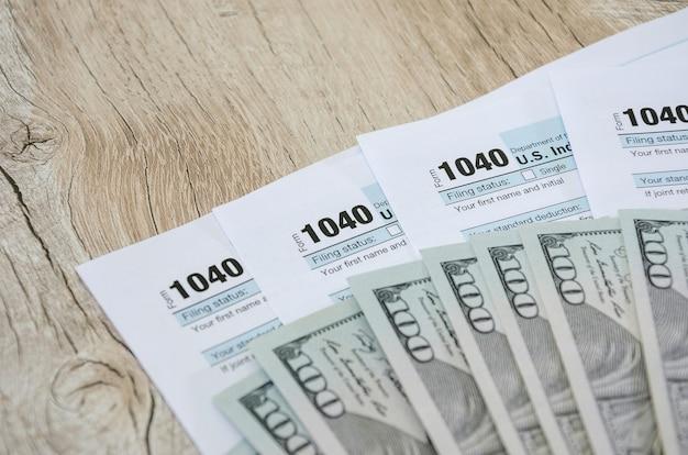 Formularze podatkowe 1040 z dolarami na drewnianym tle