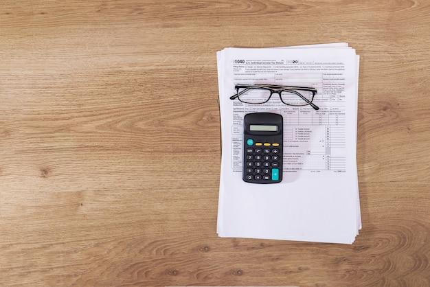Formularze podatkowe 1040 z kalkulatorem i okularami na stole. skopiuj miejsce.