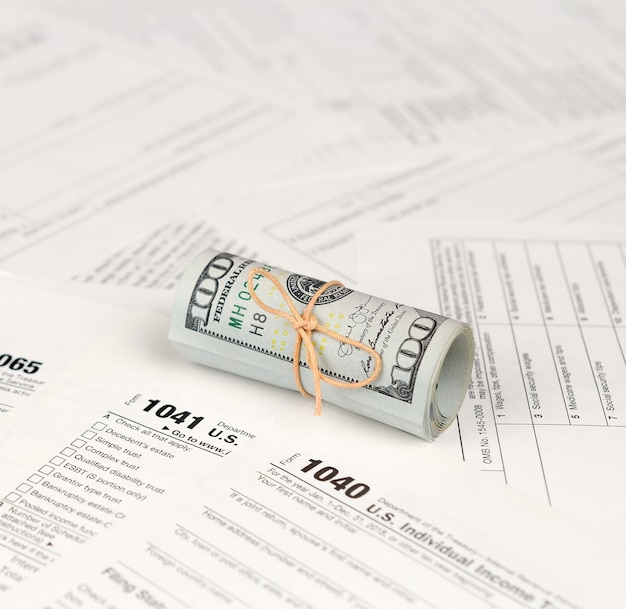 Formularze podatkowe leżą w pobliżu setek banknotów dolarowych. zwrot podatku dochodowego