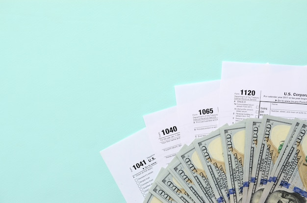 Formularze podatkowe leżą w pobliżu stu dolarowych banknotów i niebieskiego pióra na jasnoniebieskim tle. zwrot podatku dochodowego